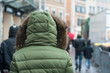 closeup of girl walking in the street with green winter coat with hood - 225553600