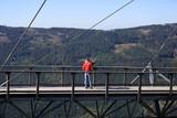 Para młodych ludzi na tarasie widokowym nad przepaścią w górach, selfie.