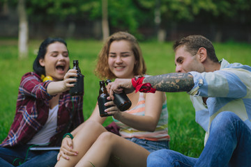 Joyful besties celebrate the occasion in a park. Students have a beer and rest after classes.