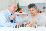 elderly couple at home playing chess
