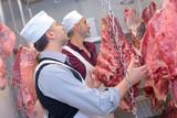 Butchers examining animal carcasses - 225561656