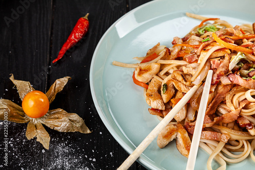 Selective focus on Chinese noodles with chicken and vegetables on dark background. Chinese cuisine, close up view, copy space for text, dark background - 225563003