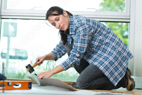 woman using hammerfor diy at home - 225564483