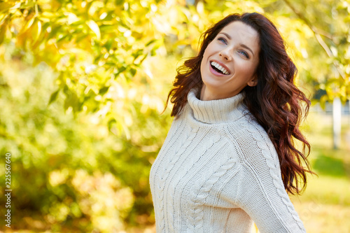 Foto Murales Autumn woman in autumn park. Warm sunny weather. Fall concept