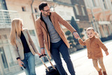 Happy family with luggage in city street
