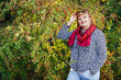 Stylish middle-aged woman posing in autumn forest. Senior lady wearing fall clothes and accessories