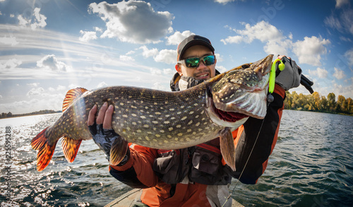 Leinwanddruck Bild Fishing. Fisherman and trophy Pike.