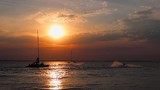 sailboat and jetskis in sea waters at sunset - 225604234