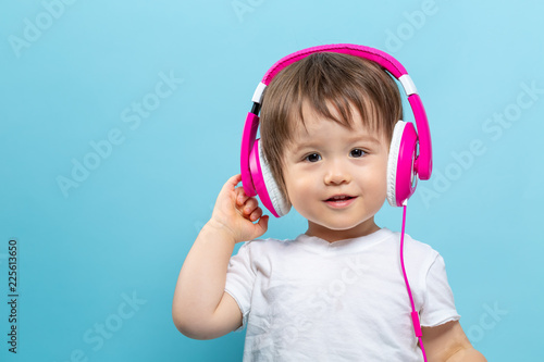 Foto Murales Toddler boy with headphones on a blue background