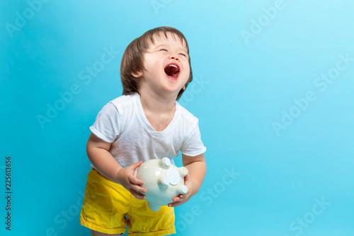 Leinwandbild Motiv Toddler boy with a piggy bank on a blue background