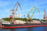 Russia, Moscow August 2018: Unloading of the barge with crushed stone port cranes in the port. - 225627075