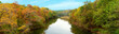 Panorama of the autumn forest along the banks of the river. Colorful autumn trees along the banks of the river. Panorama of forest and river in the autumn season.