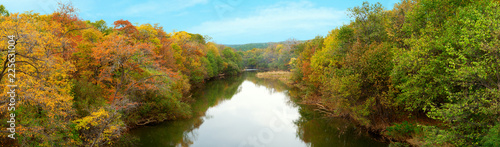 Panorama of the autumn forest along the banks of the river. Colorful autumn trees along the banks of the river. Panorama of forest and river in the autumn season. - 225631004