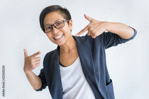 happy asian woman pointing at herself and looking at camera