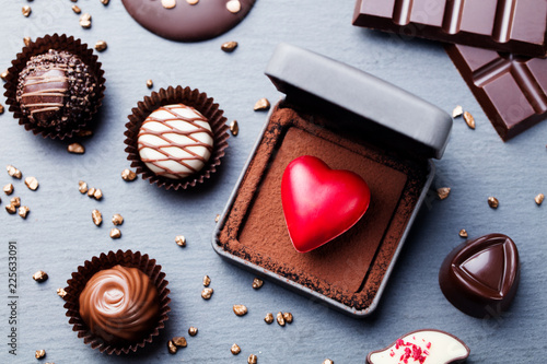 Heart shaped chocolate candy in a gift box on slate background. Top view. © annapustynnikova