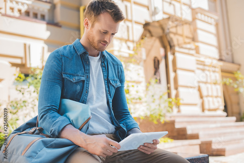 Foto Murales casual young man using tablet while sitting on street