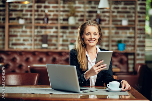 Businesswoman using tablet while sitting in cafeteria. On table laptop and coffee.