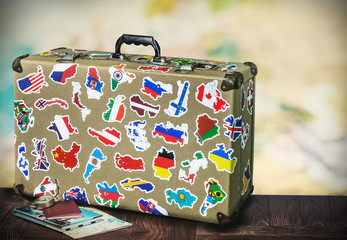 old suitcase with stikkers on the floor against the backdrop of a world map. Toned image