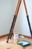 Freshly painted light blue room with painting equipments at home and ladder. Painting accessories are in an empty room.