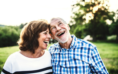 A laughing senior couple in love outdoors in nature.