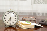 old metal alarm clock, glasses, book, wallet on the table near t - 225676439