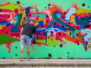 young man use his talent and feeling for art to apply this with various colors to a city wall