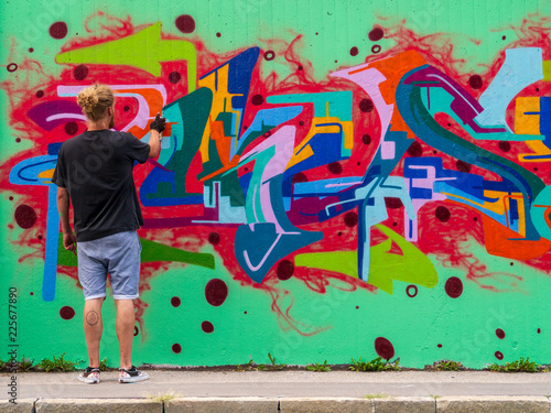 young man use his talent and feeling for art to apply this with various colors to a city wall - 225677890