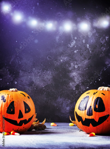 Halloween composition with pumpkins lanterns, with fallen leaves on a dark blue background, selective focus