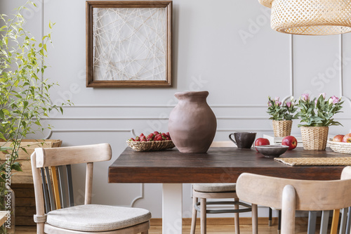 Wooden chairs at table with vase and flowers in grey dining room interior with poster. Real photo