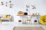 Real photo of a modern home office interior with graphics, desk, sofa and yellow pouf - 225687800