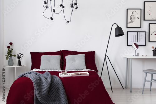 Leinwandbild Motiv A burgundy bedding and gray pillows on a bed in a white wall bedroom interior. Real photo.