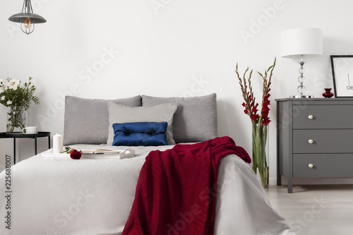 Leinwanddruck Bild Glamour bedroom interior with a bed dressed in gray linen and cushions with contrasting accents of blue and red. Real photo.