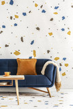 Wooden table in front of blue couch with orange pillow in colorful living room interior. Real photo
