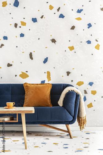 Drewniany stół przed błękitną leżanką z pomarańczową poduszką w kolorowym żywym pokoju wnętrzu. Prawdziwe zdjęcie