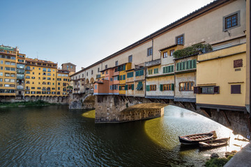 Backlit view of the famous Ponte Vecchio bridge in Florence, Italy on a stunning summer day