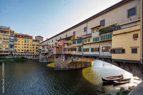 Backlit view of the famous Ponte Vecchio bridge in Florence, Italy on a stunning summer day - 225690880