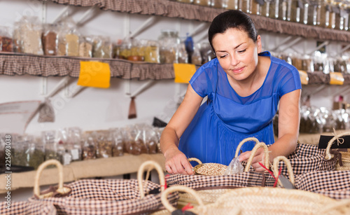 female customer buying dried seeds by weight in shop with organic products