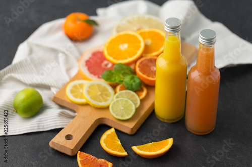 food , healthy eating and vegetarian concept - glass bottles of orange and grapefruit juice and citrus fruits on slate table top