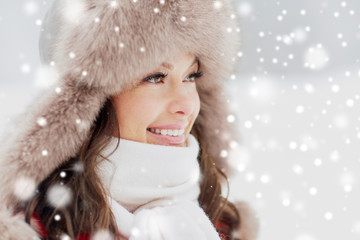 people, season and leisure concept - close up of happy woman in winter fur hat outdoors