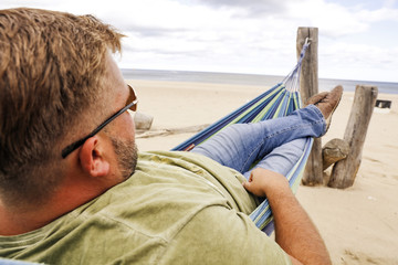 Beach and sea landscape with man on hammock.