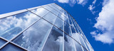 modern blue glass and metal office facade reflects clouds and blue sky