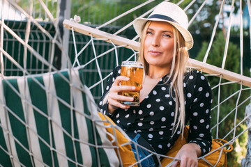 Blonde Woman Drinking Beer in Hammock © ardaakay