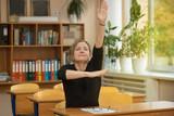 Студентка сидит за партой в классе и тянет вверх руку  - 225708635