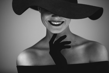 Elegant beautiful woman in a black dress and hat