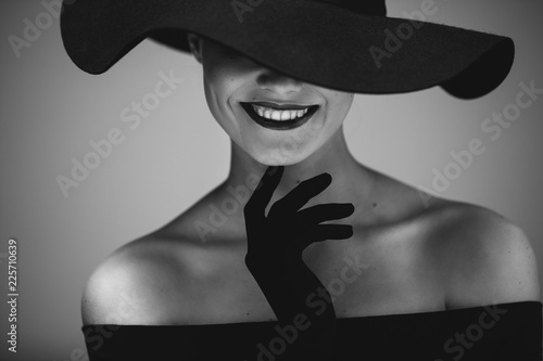 Leinwandbild Motiv Elegant beautiful woman in a black dress and hat
