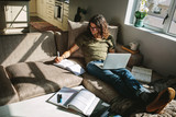 Student studying at home sitting beside a window