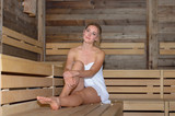 Young smiling blonde woman relaxing in sauna