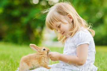 Girl with a cute little rabbit, outdoor, summer day © Natalia Chircova