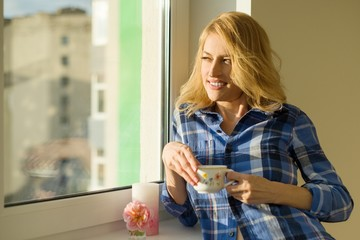 Mature beautiful blonde woman looks out the window in the apartment, drinks coffee