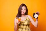 Asian woman with a clock drink orange juice. - 225735289